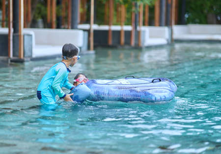 Boy and girl play floater in big swimming pool near under water stairs on blur sofa background in weekend holiday happy concept