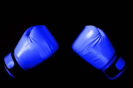 Blue Boxing glove in punching  in black background with copy space Reklamní fotografie