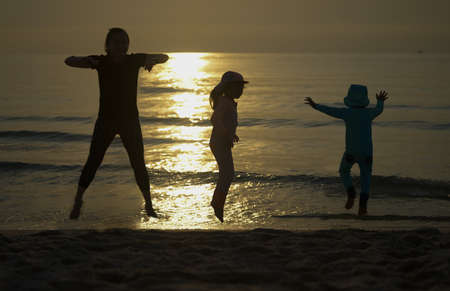 mom son and daughter jumping at beach front togetherness