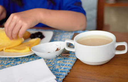 Cup or bowl of soup on blur plate with crape and jam and hand while eating breakfast