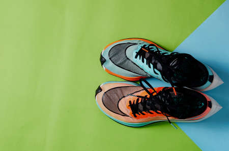 Blue and orange running shoes on green floor with copy test space