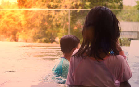 Boy  and girl play water near poolside in swimming pool in summer vacation