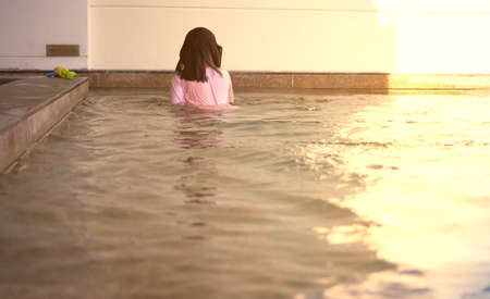 Back of kid girl play water in swimming with sun light