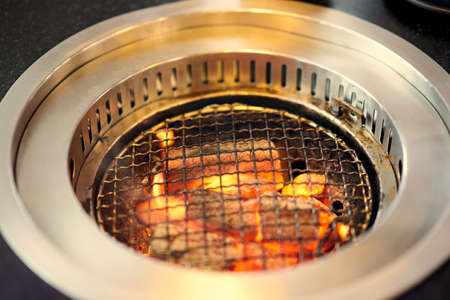 Charcoal grill with grating on fire with smoke suction
