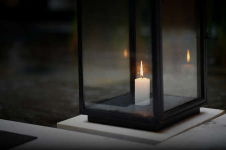 Candle in glass housing on floor in dark time with flame Reklamní fotografie