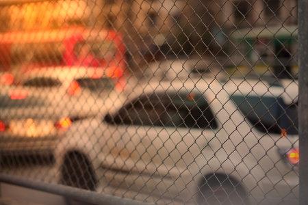 Metal net  fence view on sun light traffic jam background Reklamní fotografie