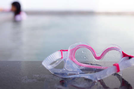 Goggles on poolside of swimming pool on blur kid in water background in summer beach holiday concept