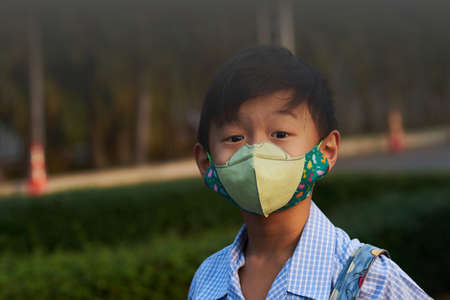 boy with N95 mask protection from PM 2.5 dust crisis at school in pollution concept