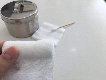 finger tip hold roll gauze on blur swab and gauze jar in medical concept