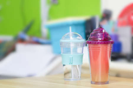 two plastic themal preserve cup color and transparent on table in room