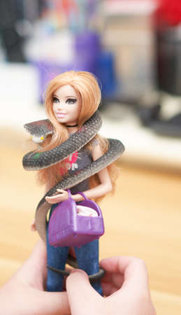 Bangkok,Thailand,Aug 17,2021-hand hold play barbie doll in costume bag with snake fantacy