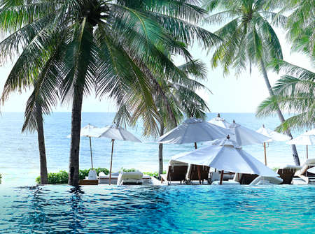 Beach pool and umbrellas and chair with coconut trees and sky in hotel resort Banque d'images