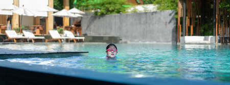 asia little girl with gogles swim in swimming pool in hotel resort beach front in holiday vacation Banque d'images