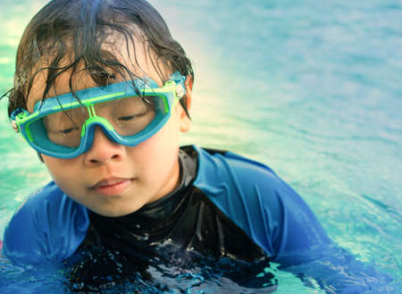young boy in goggles in swimming pool