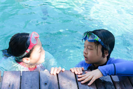 Kids hold on poolsidein swimming suit play and swim in water pool in resort Banque d'images