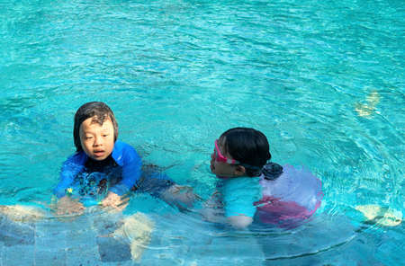 kids in swimming suit play and swim in water pool in resort