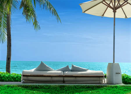 Sofa chairs set overlooking the beach, sea, beach umbrellas, coconut trees and green grass. blue sky and grass