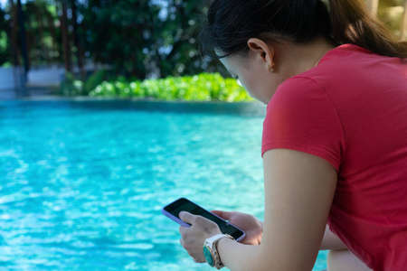 woman sit poolsie using smartphone technology beside swimming pool for social media Banque d'images