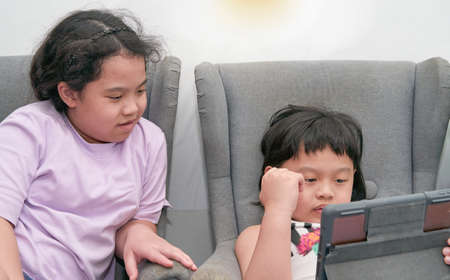 Gadget addiction asia two kids sit on armchair sofalook at tablet computer on on white