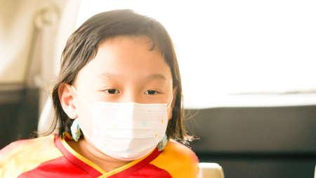 Asia boy wear protective mask in car travel in quarantine coronavirus Covid-19 pandemic in car cabin
