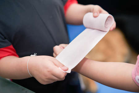 elastic roll gauze bandage hold in hand with adhesive for first aid compress care for accident applying