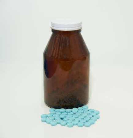 blue Pills medical tablets on floor beside bottle on white portrait Banque d'images