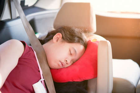 Asian girl kid sleep in car with pillow and seatbelt for safety ride car travel concept