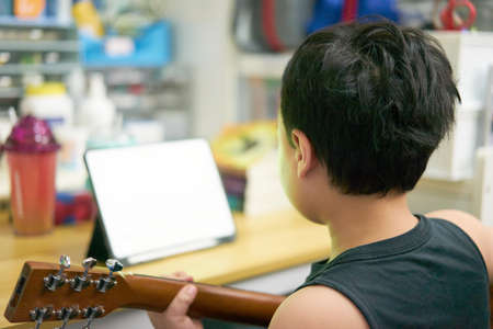 asia boy learn play guitar online by tablet notebook computer in room home back view