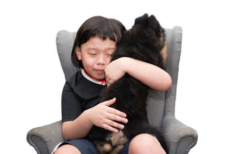 asia boy sit on armchair and hug pet dog with happy isolated on white