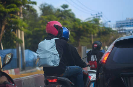motorcycle passenger with safety helmet same as rider on street road traffic view in Bangkok asia Thailand Banque d'images