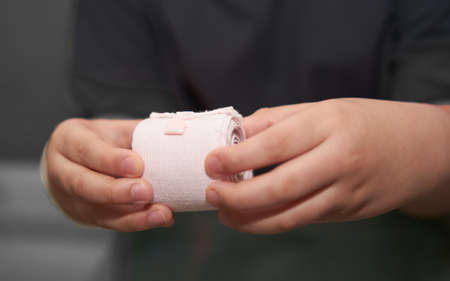 elastic roll gauze bandage hold in hand with adhesive for first aid compress care for accident side view