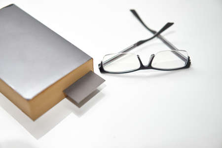Bookmark in old book on white high angle view with copy space with read glasses