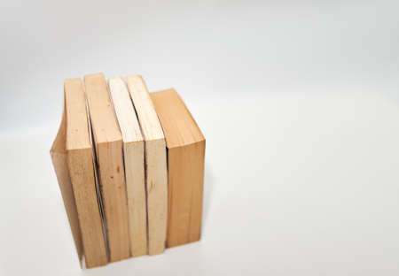stacks of books arranged horizontally on white background high angle view