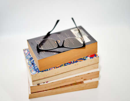 stack of books arranged pile on white background with glasses on top high angle view Banque d'images