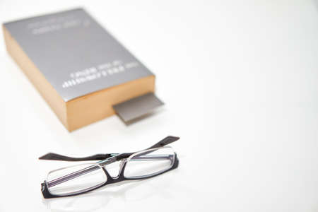 read glasses selective focus on blur Bookmark in old book on white background high angle view