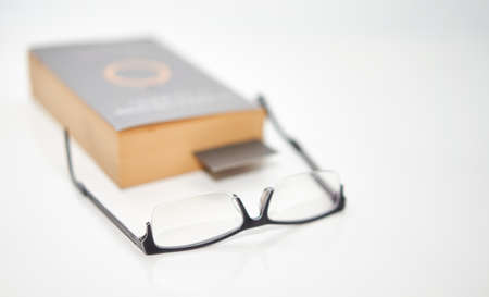 read glasses selective focus on blur Bookmark in old book on white background Banque d'images
