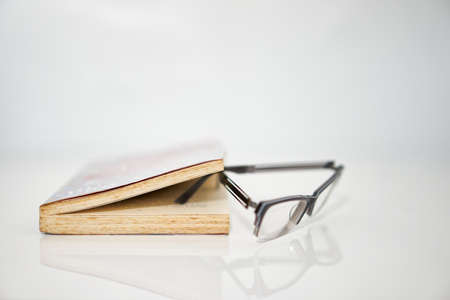 Open book on white with reading glasses with copy space