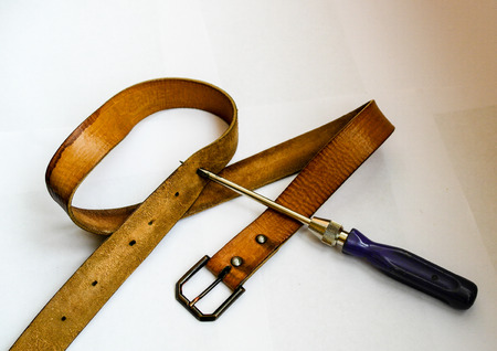 tighten: to make a new hole in the belt to tighten their belts Stock Photo