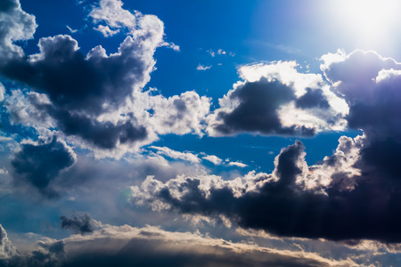 Sun and White and dark Cumulus clouds on a blue sky photo