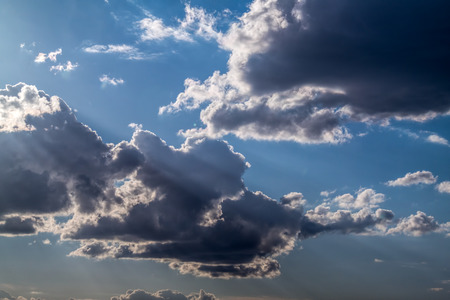 nebulosity: White and dark Cumulus clouds on a blue sky Stock Photo