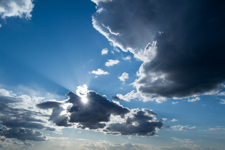 the rays of the Sun, and white and dark Cumulus clouds on a blue sky photo
