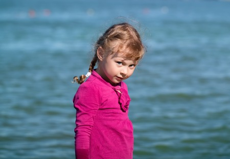 blue eyes: little girl with blue eyes in a raspberry dress looking slyly at the background of water