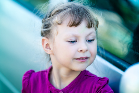 admires: little girl in purple dress admires itself in the mirror of the car