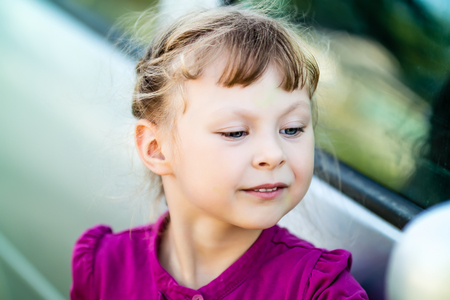 self conceit: little girl in purple dress admires itself in the mirror of the car
