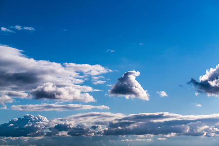 cumulus: the rays of the Sun, and white and dark Cumulus clouds on a blue sky