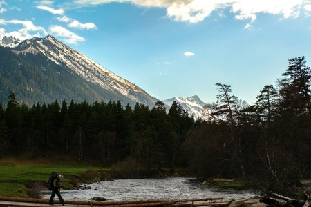 The man is crossing the log across the river