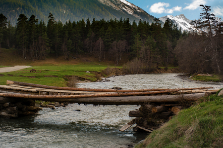 Crossing the logs across the river in the mountains of Arhyz against the background of the peaks