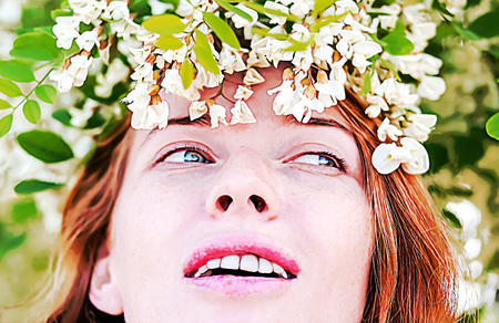 Redhead model among Flowers acacia Stock Photo
