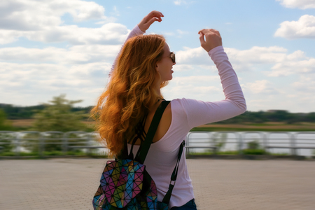Redhead model dances against the sky Фото со стока