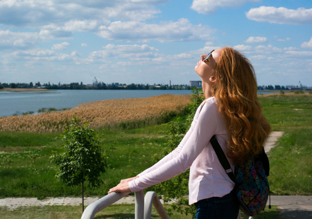 The redhead model rejoices at the sun in nature